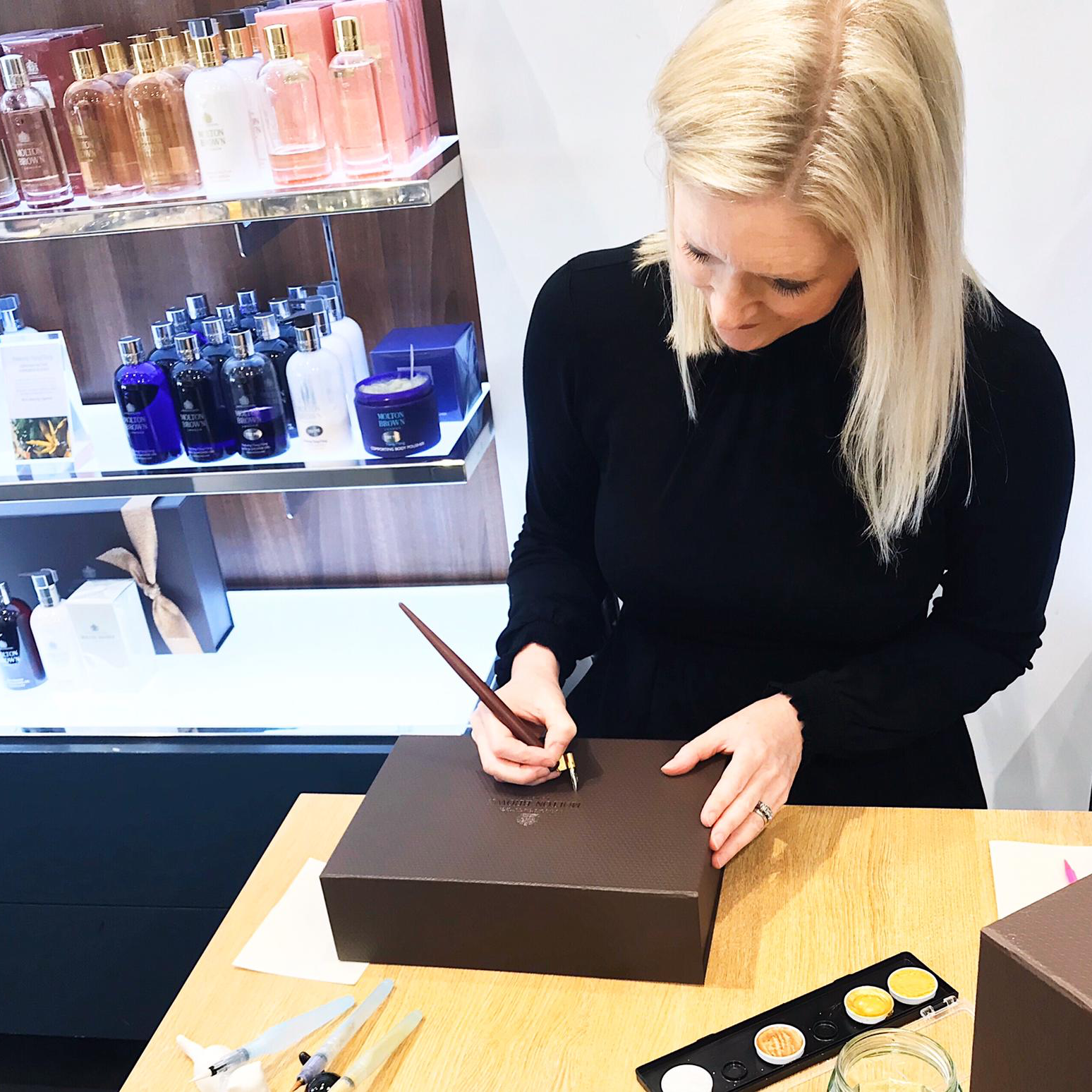 Laura Prudence creating elegant calligraphy on Molton Brown packaging at a Brighton event.