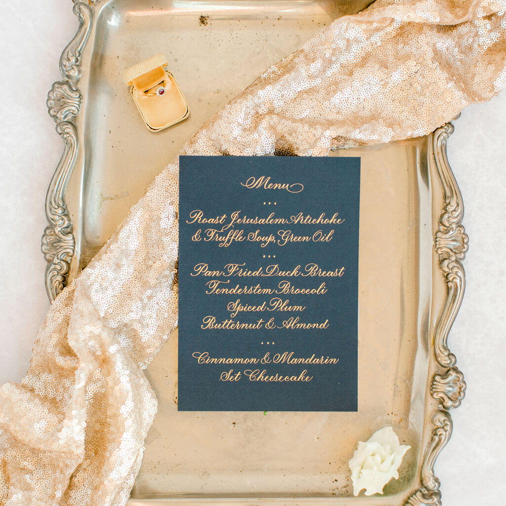 Sophisticated dinner menu hand lettered in elegant gold copperplate calligraphy on luxury navy blue card.