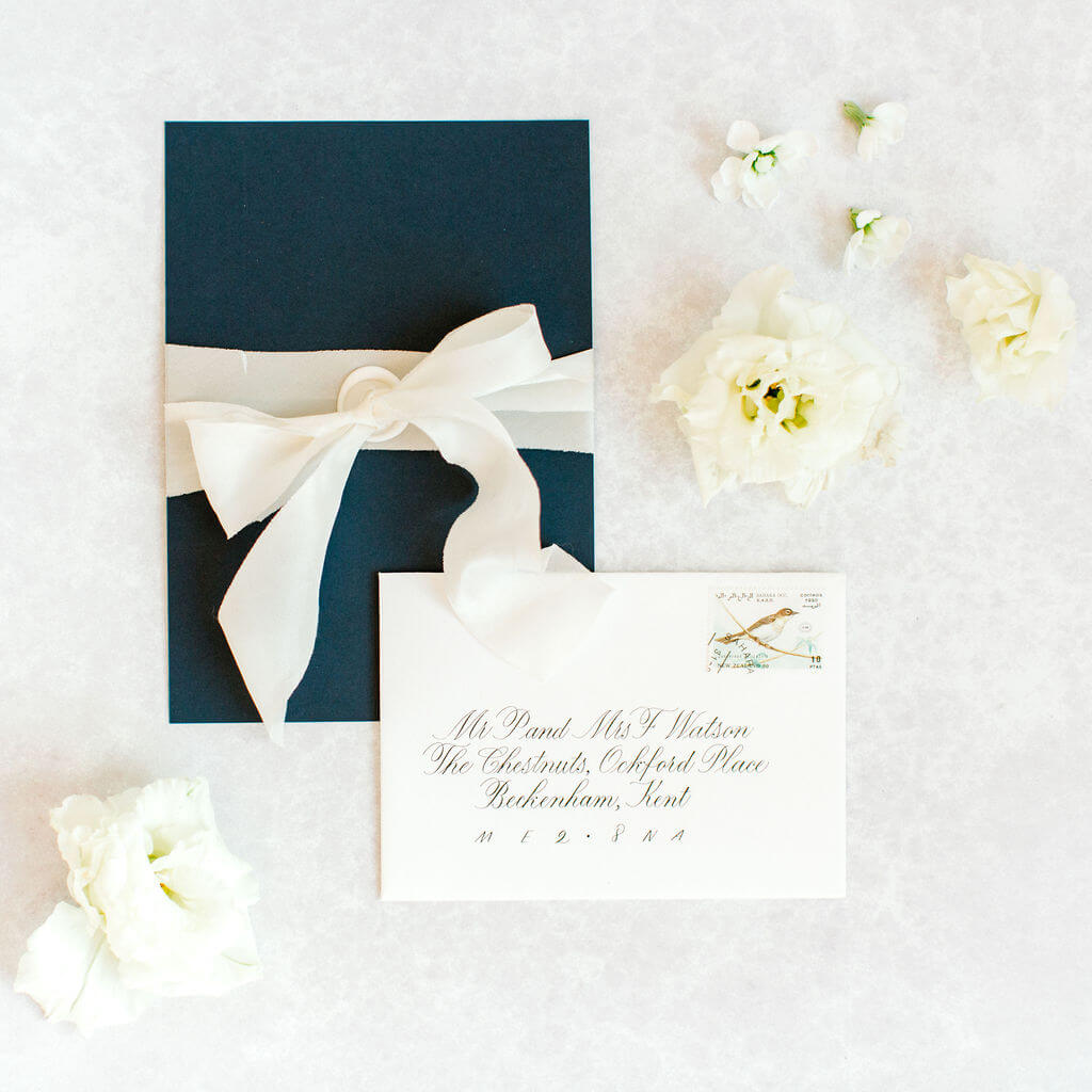 Crisp white luxury envelope hand lettered in elegant classic copperplate calligraphy.