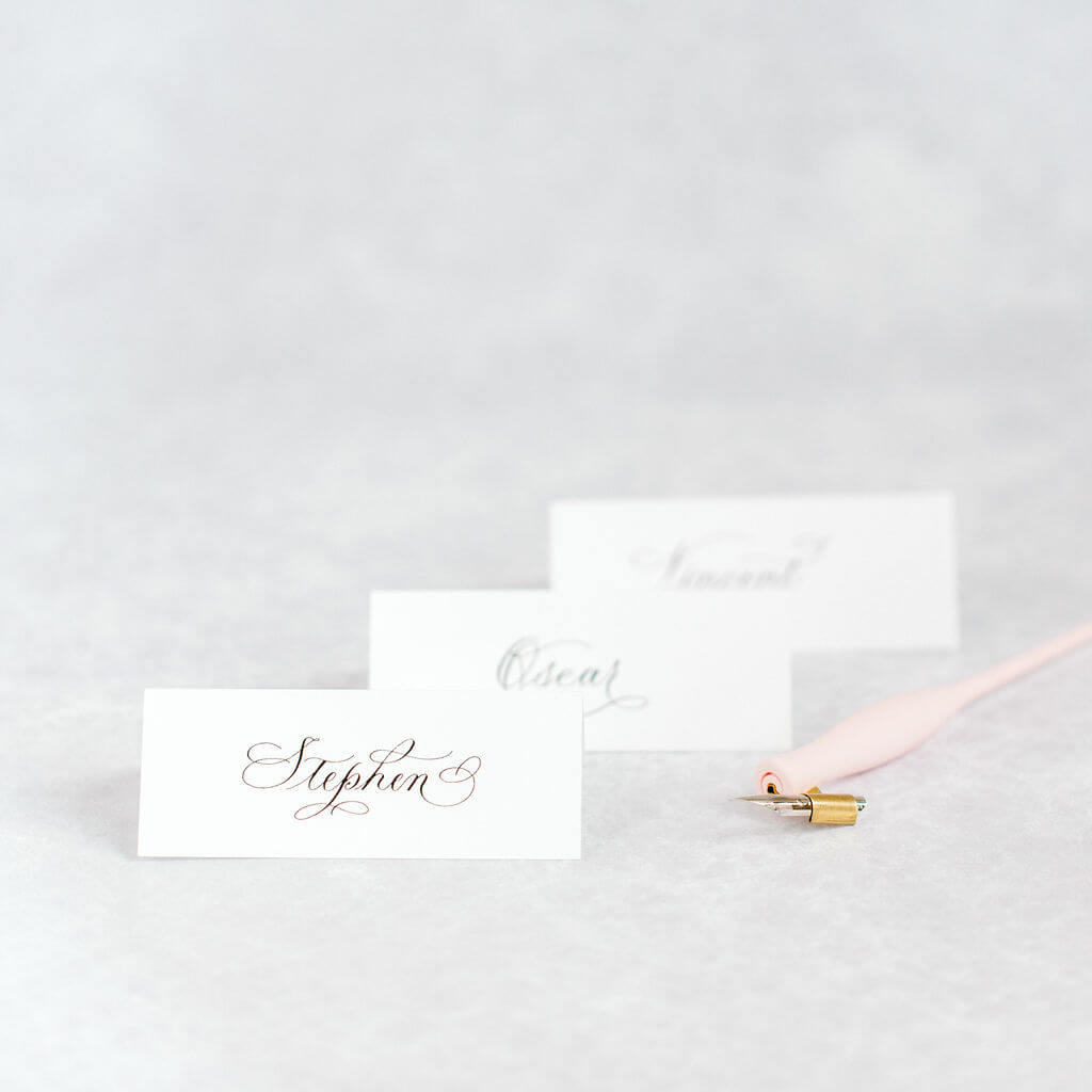 Classic white place cards hand lettered using black ink in an elegant flourished copperplate style.