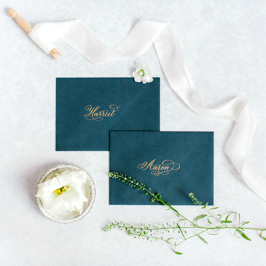 Sophisticated gold flourished copperplate calligraphy hand lettered on luxury navy blue envelopes.