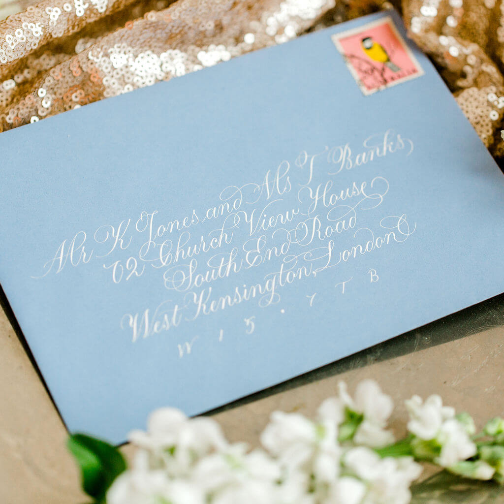 Sophisticated and elegant flourished copperplate calligraphy hand lettered in white ink on a beautiful blue envelope.