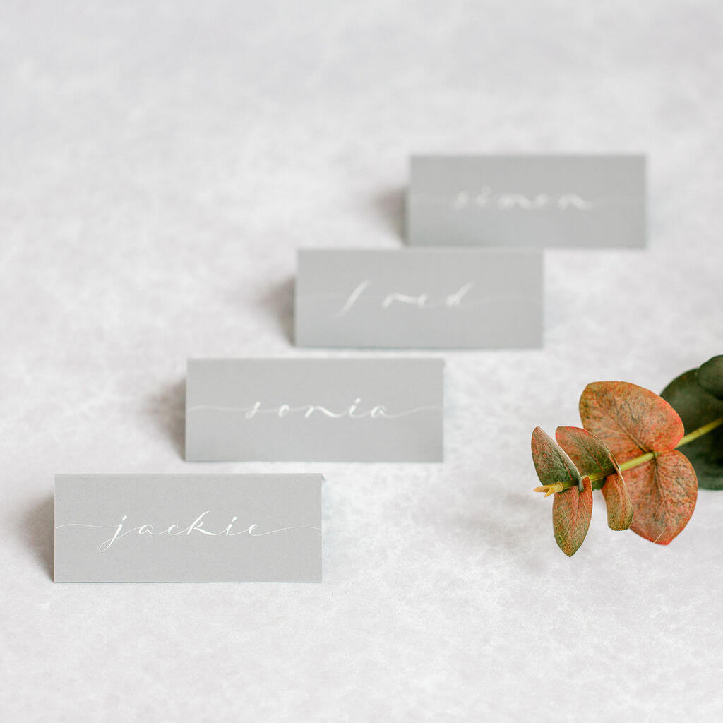 Elegant elongated modern calligraphy style hand lettered onto luxury grey place cards.