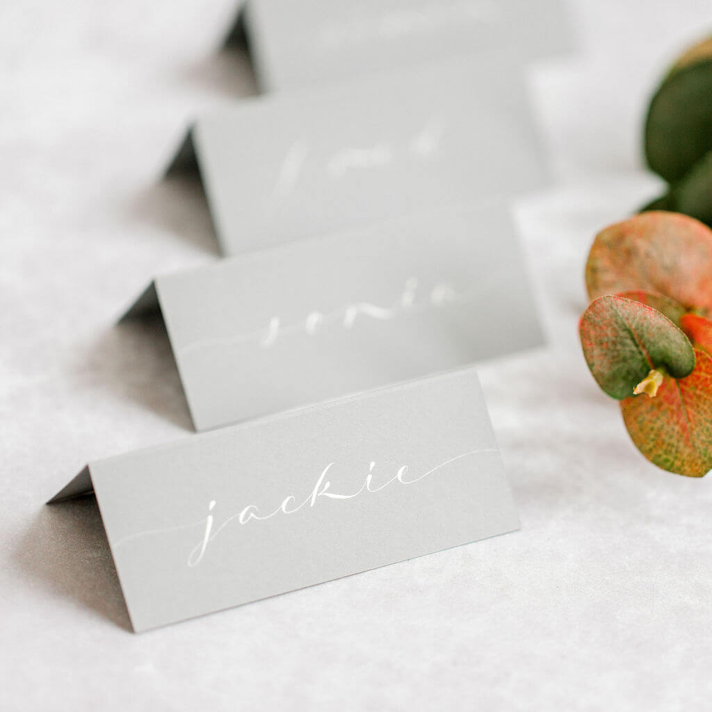 A modern calligraphy script handwritten in white ink on classic grey place cards.