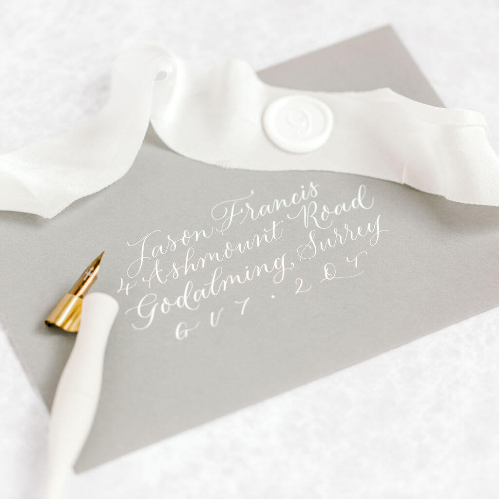 Elegant white modern calligraphy handwritten onto a luxury grey envelope.