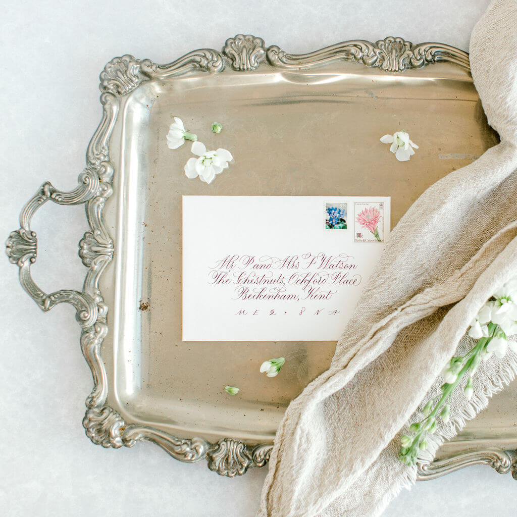 Sophisticated flourished copperplate calligraphy elegantly hand lettered on a luxury bright white envelope.