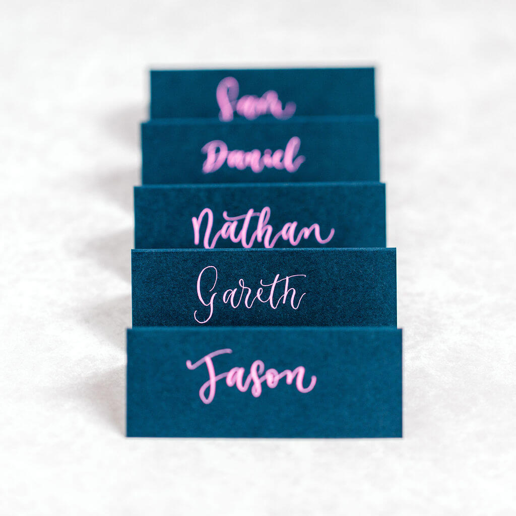Place cards hand lettered in a stylish, modern, pink calligraphy style