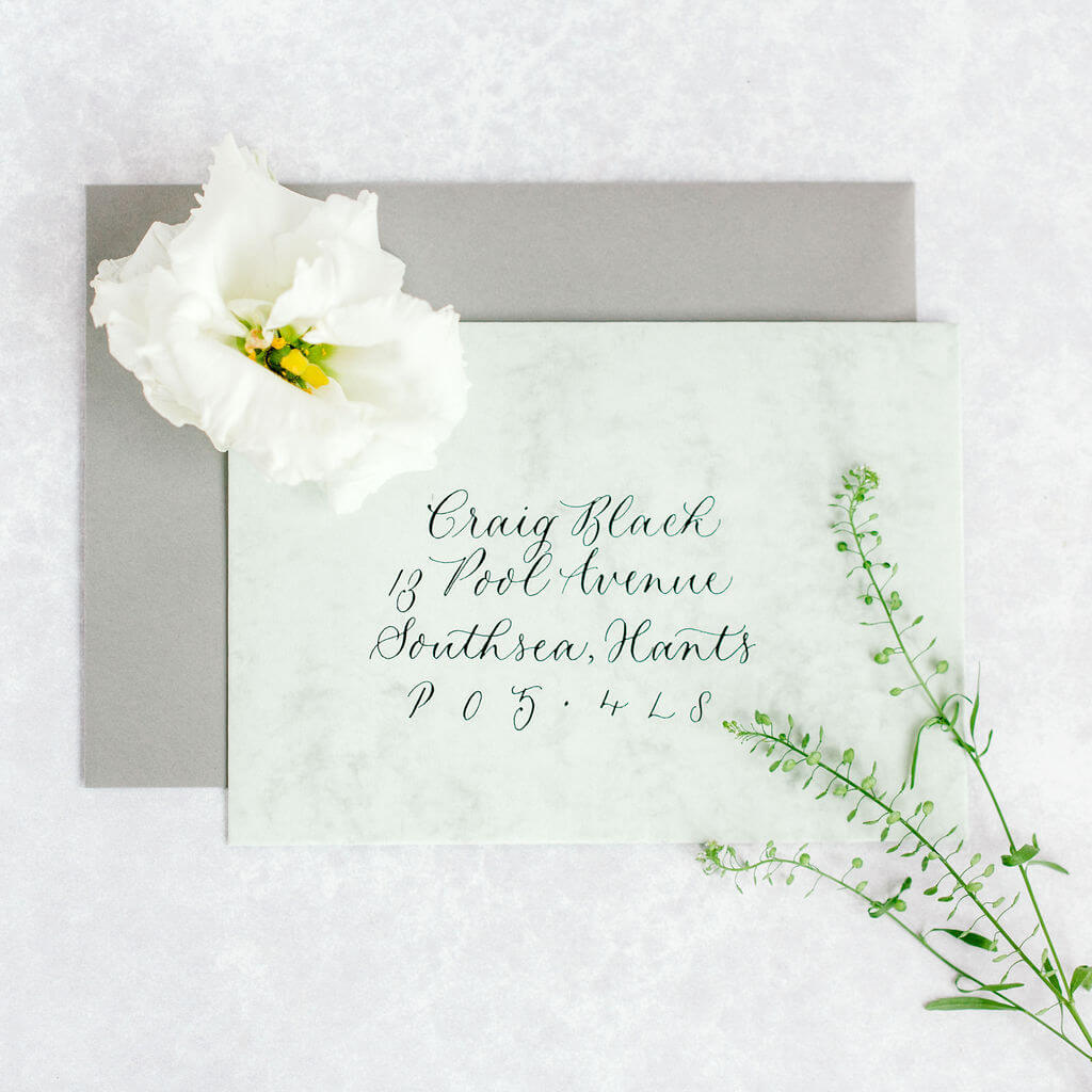 Sophisticated modern calligraphy on a luxury green marbled envelope.