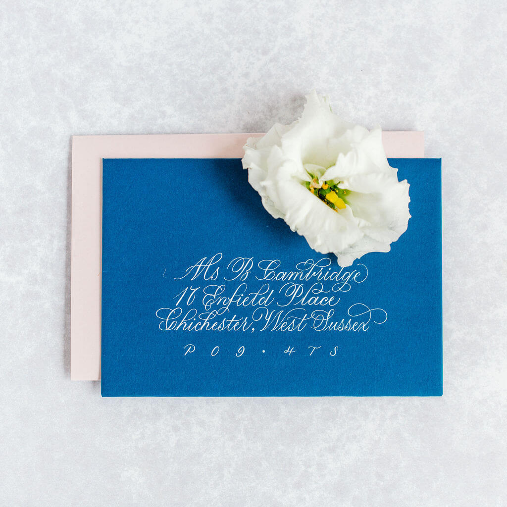 Luxurious flourished copperplate calligraphy on a luxury blue wedding envelope.