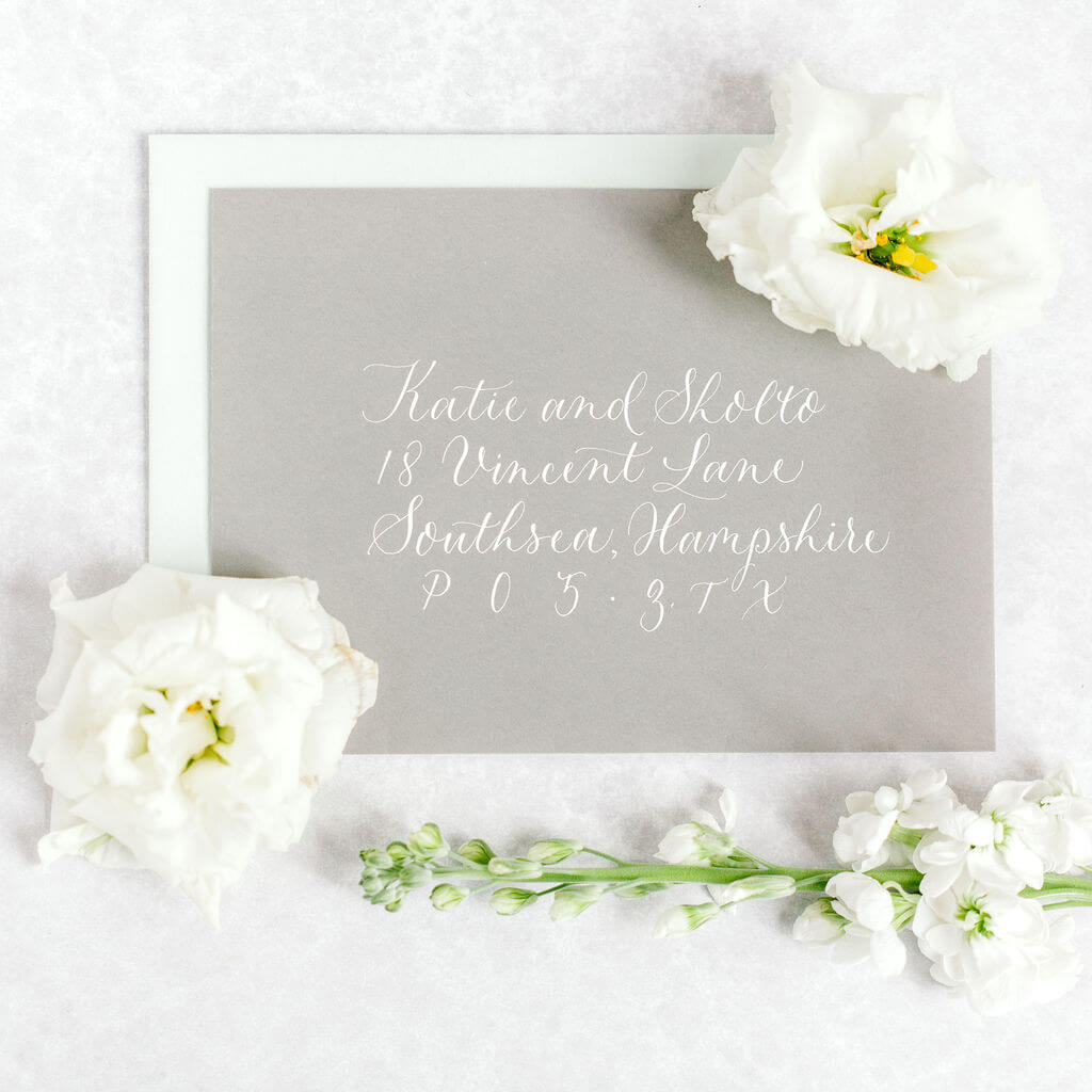Stylish and elegant modern calligraphy created with a classic combination of white ink on a luxury grey envelope.