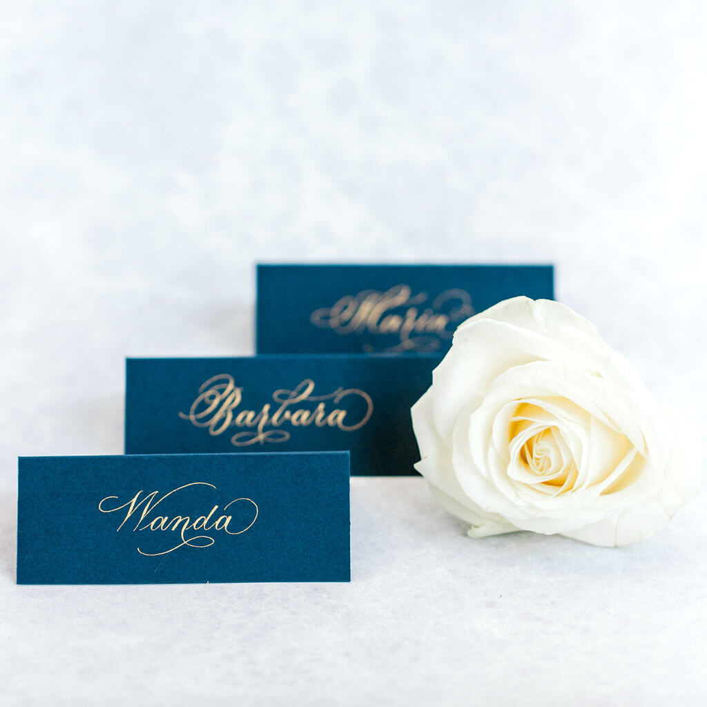 Sophisticated gold flourished copperplate calligraphy handwritten in gold ink on luxury navy blue place cards.