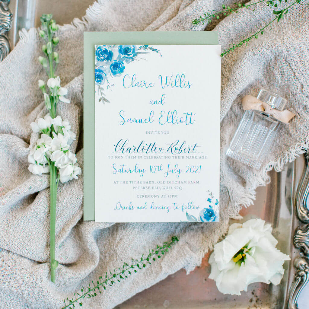 A contemporary wedding invitation with guests' names hand lettered in a modern calligraphy script, presented on an antique tray.